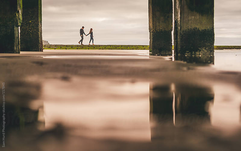 Couple walking under a pier by Sam Hurd Photography for Stocksy United