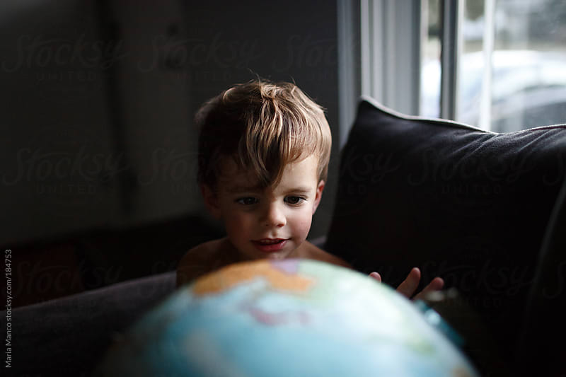 child looks at globe by Maria Manco for Stocksy United