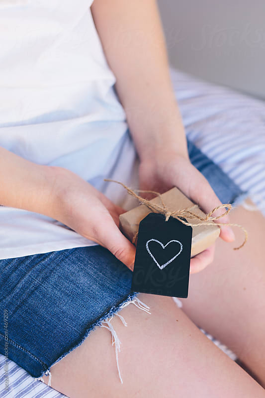 Teenage girl sitting on her bed holding a small gift with a heart shape drawn on the tag by Jacqui Miller for Stocksy United