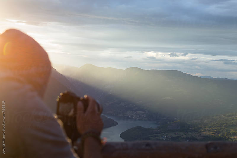 Man filming nature from a viewpoint at sunset by Jovana Milanko for Stocksy United