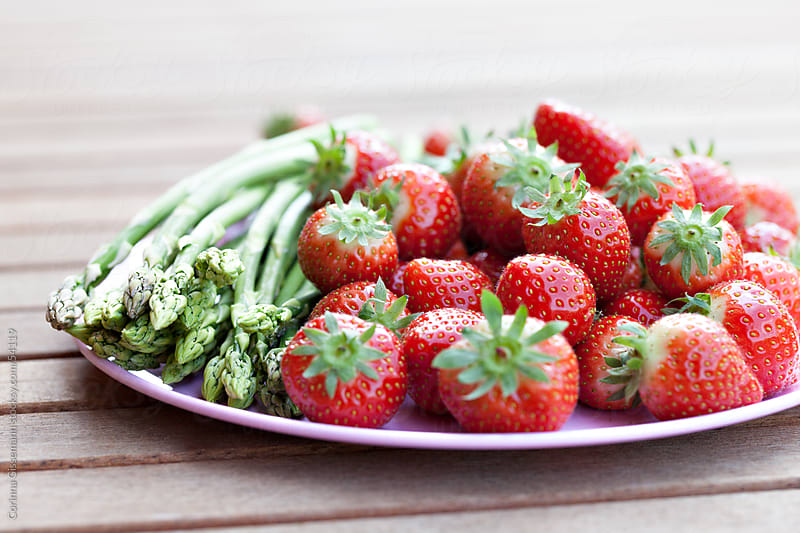 a group of fresh red strawberries and green raw asparagus on a plate by Corinna Gissemann for Stocksy United