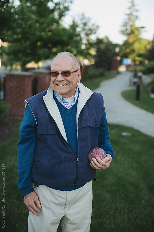 Happy, healthy caucasian senior man playing fun game of bocce ball outside by Rob and Julia Campbell for Stocksy United