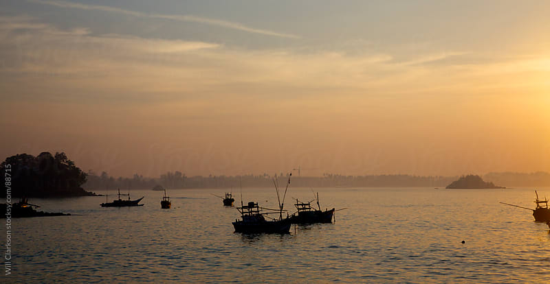 Fishing boats lie at mooring on a coast at sunrise by Will Clarkson for Stocksy United