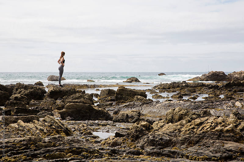 Woman standing on rocks at the beach by Curtis Kim for Stocksy United