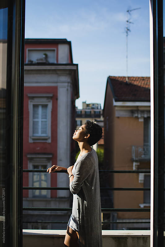 Attractive young girl enjoying the sun on the balcony by michela ravasio for Stocksy United