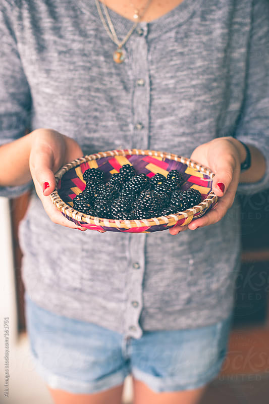 Girl holding punnet of fresh blackberries by Aila Images for Stocksy United