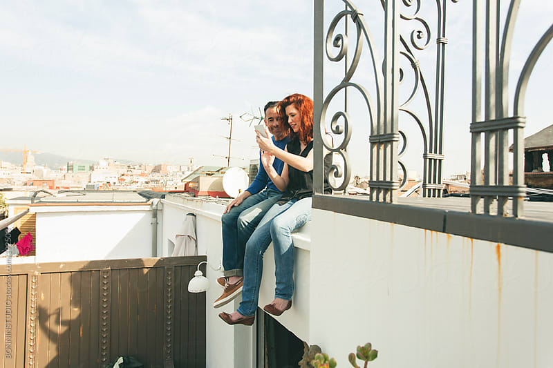 Beautiful couple using one smart phone sitting on the rooftop. by BONNINSTUDIO for Stocksy United