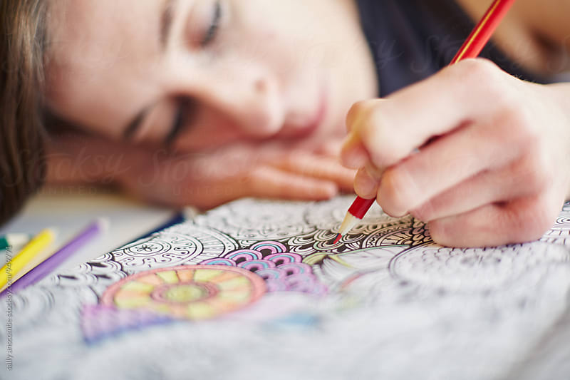 Young woman colouring in an adult colouring in book by sally anscombe for Stocksy United