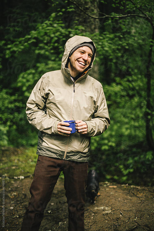 Smiling man outdoors holding a camping mug by Kristine Weilert for Stocksy United