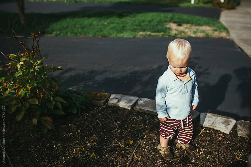 A Young Toddler Boy Stands Outside in the Bark looking Down by Amanda Voelker for Stocksy United