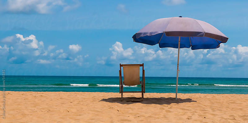 Beach Chair and Umbrella on a tropical sunny beach by Caine Delacy for Stocksy United
