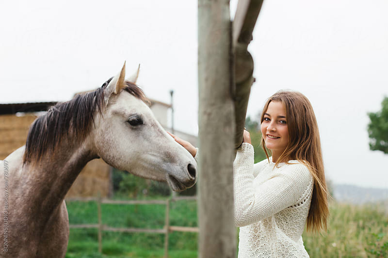 Teen girl with her horse on a farm. by BONNINSTUDIO for Stocksy United