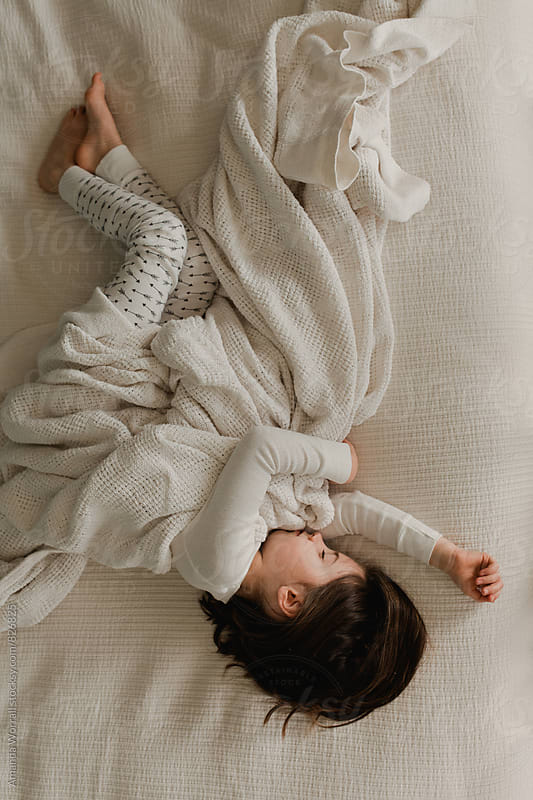 Young girl snuggling with a neutral blanket, resting on bed by Amanda Worrall for Stocksy United