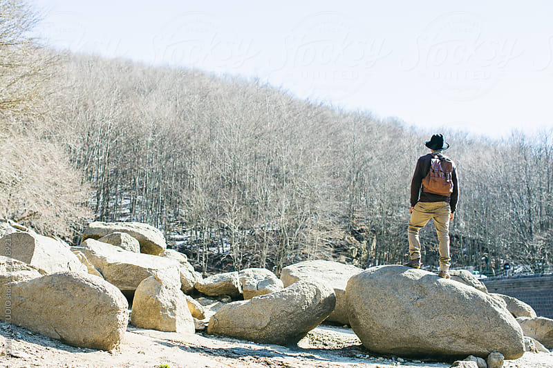 Back view of a mountaineer on a big stone enjoying the nature. by BONNINSTUDIO for Stocksy United