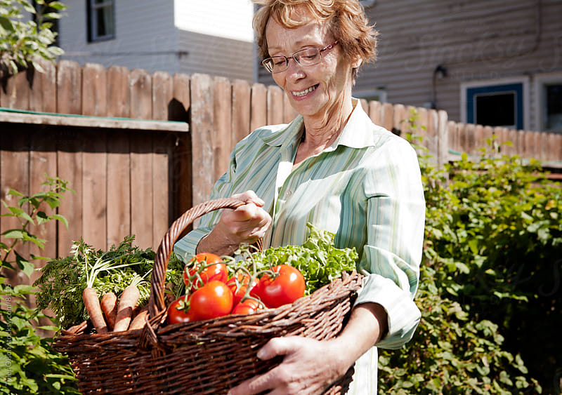Senior Woman Holding Garden Vegetables by Tyler Olson for Stocksy United