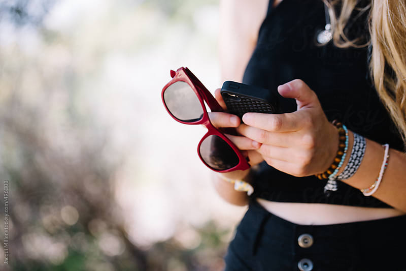 Close up of teen girl holding a mobile phone and sunglasses, with copyspace by Jacqui Miller for Stocksy United