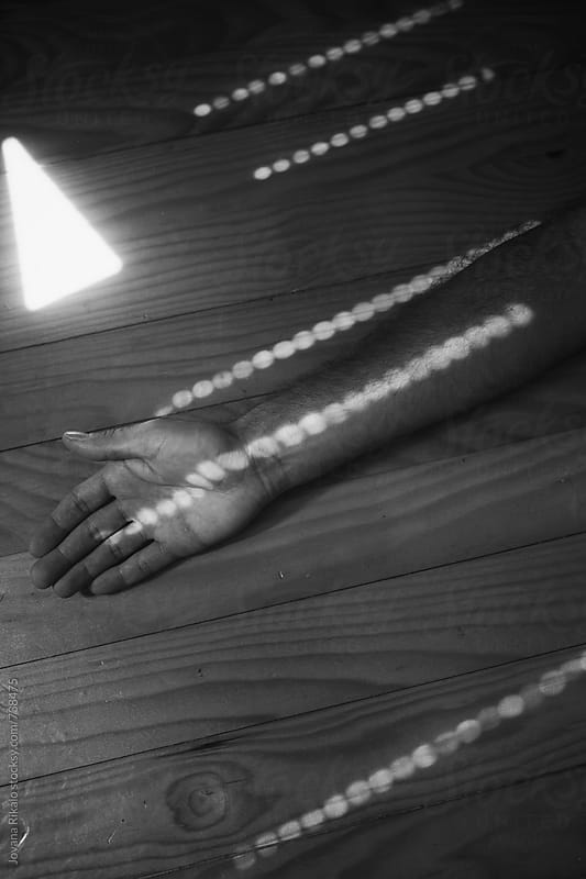 Black and white photo of hands on floor with sunlight spots all round by Jovana Rikalo for Stocksy United