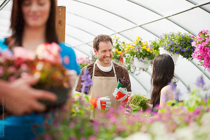 Nursery: Helpful Employee Gives Customer Advice by Sean Locke for Stocksy United