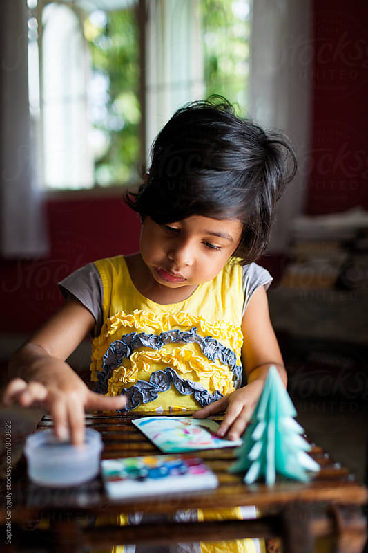 Little girl trying to make a greetings card with watercolor by Saptak Ganguly for Stocksy United