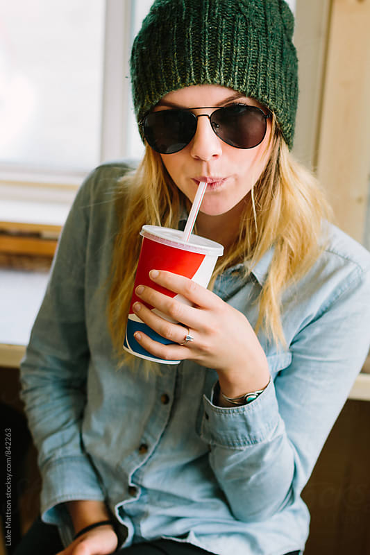 Stylish Young Woman Wearing Sunglasses Sitting In Restaurant Drinking Soda Through Straw by Luke Mattson for Stocksy United