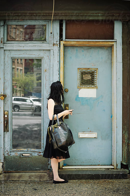 Woman in Little Black Dress with Cellphone Waiting outside a Residential Door by Joselito Briones for Stocksy United
