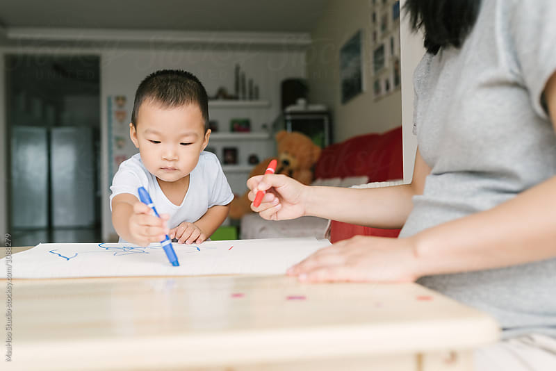 Toddler boy and his pregnant mother drawing at home by Maa Hoo for Stocksy United