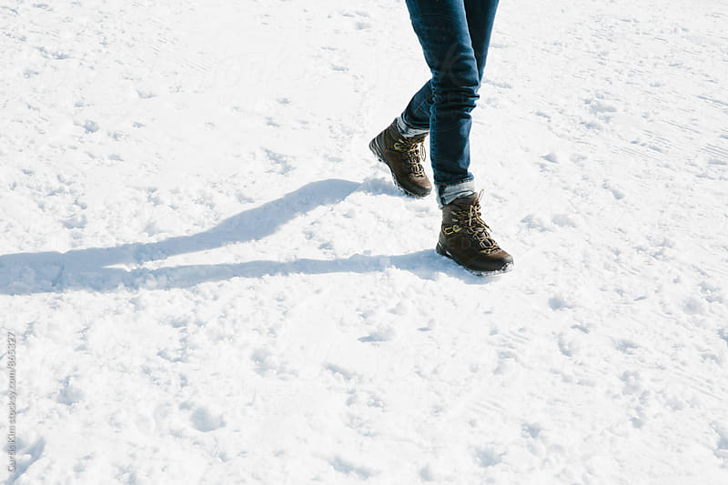 Walking on snow wearing hiking boots by Curtis Kim for Stocksy United