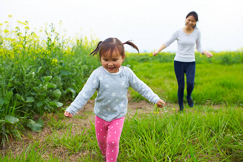 little asian girl running outdoor with her mother after by Bo Bo for Stocksy United