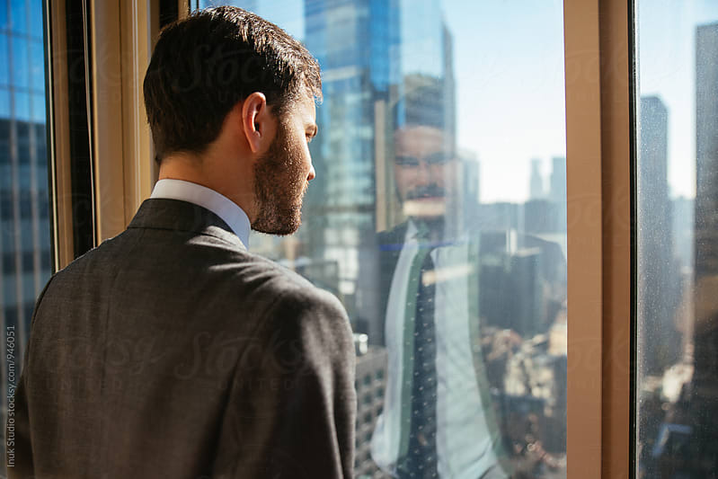 Young businessman looking out of a window in an office in tall building by Inuk Studio for Stocksy United