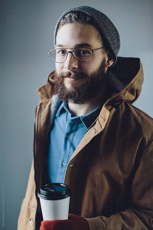 Bearded man in a jacket with a coffee by Ania Boniecka for Stocksy United