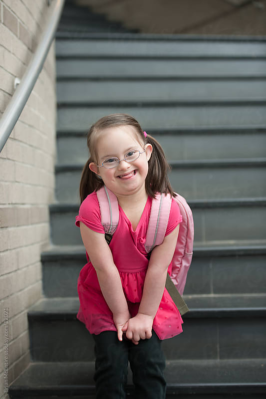 Adorable First Grader with Down Syndrome Makes Wide Grin on School Stairway by Brian McEntire for Stocksy United