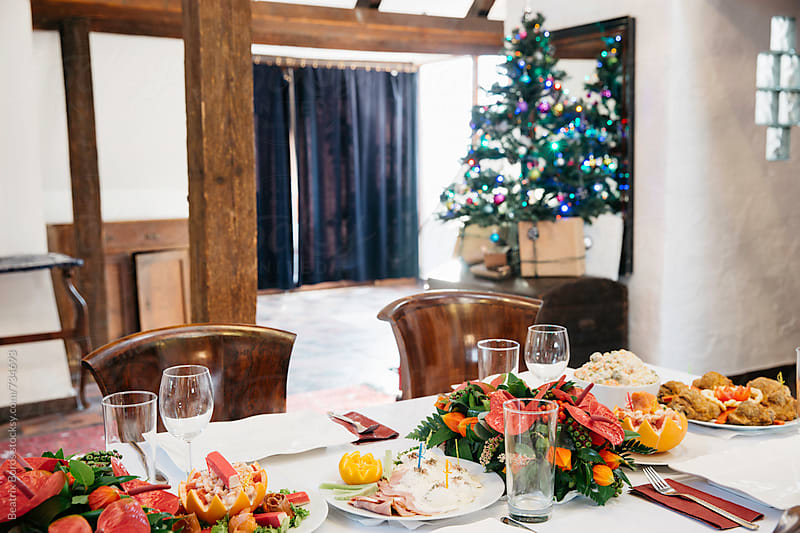 Nicely decorated Christmas table with a Christmas tree in the background by Beatrix Boros for Stocksy United
