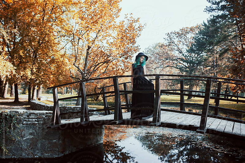 Young woman in a black dress standing on a wooden bridge by Jovana Rikalo for Stocksy United