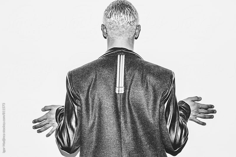 fashionable blond guy in stylish leather jacket in front of a white wall, direct light by Igor Madjinca for Stocksy United