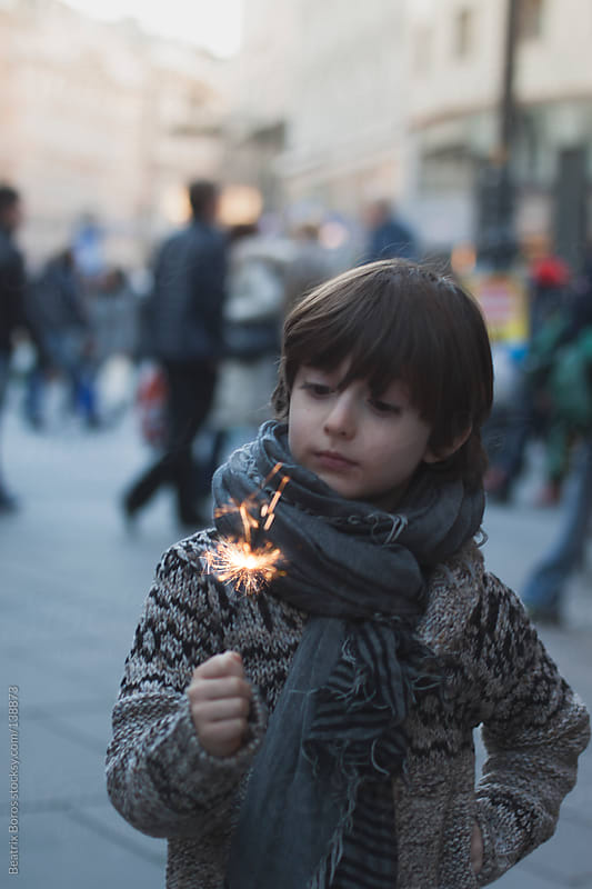 Boy holding a sparkler in the street by Beatrix Boros for Stocksy United