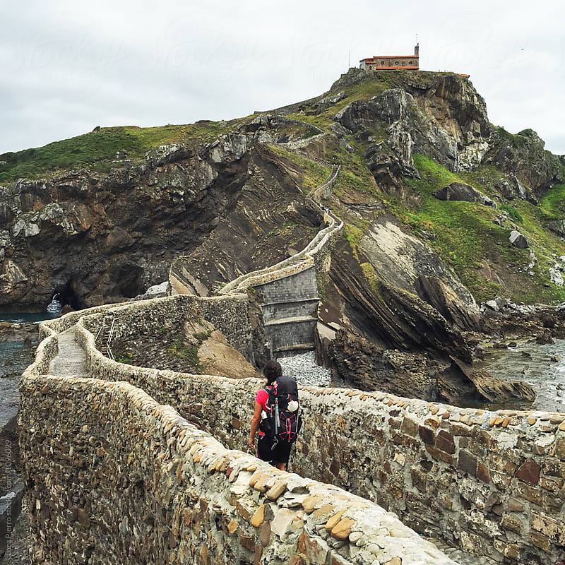 Female hiker going up the path to San Juan de Gaztelugatxe by Luca Pierro for Stocksy United