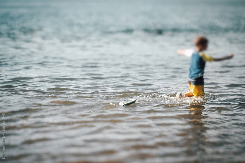 young child pulling a little toy boat on a lake by Léa Jones for Stocksy United