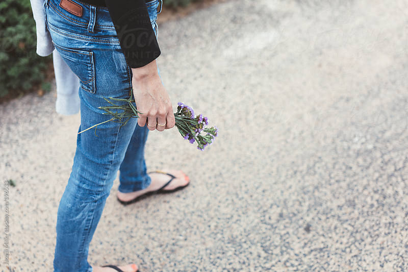 Woman wearing blue denim pants is walking a long a road holding wild flowers in her hand  by Jacqui Miller for Stocksy United
