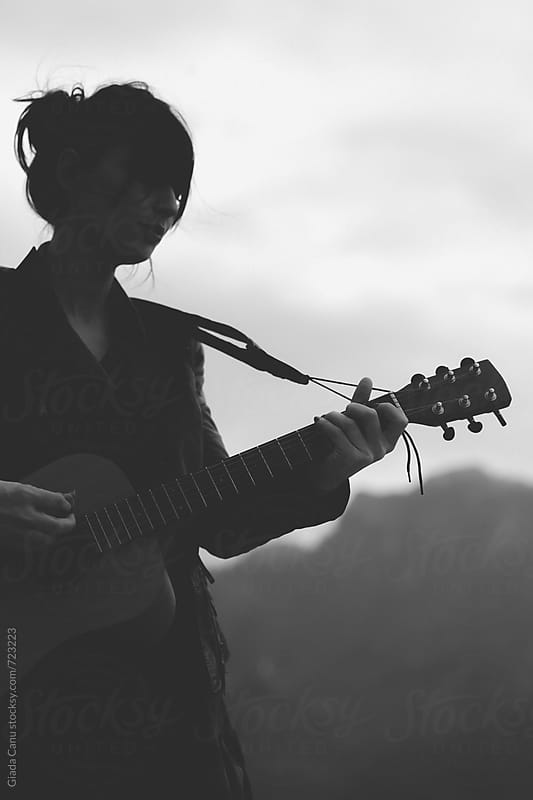 Woman playing guitar in nature by Giada Canu for Stocksy United