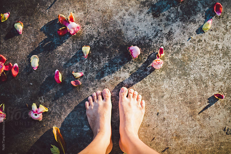 Woman feet selfie on the grey concrete with flowers on the floor by Nabi Tang for Stocksy United