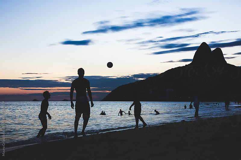 Brasil, Rio De Janeiro, silhouette of people playing with ball on Ipanema Beach by Mauro Grigollo for Stocksy United