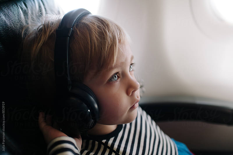 Little girl listening to headphones on a plane. by Julia Forsman for Stocksy United