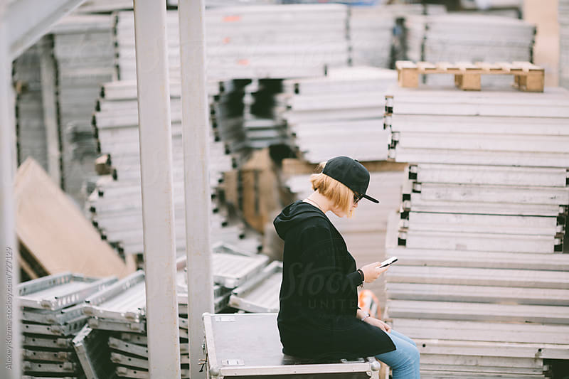 teen girl with smartphone near industrial crates by Vesna for Stocksy United
