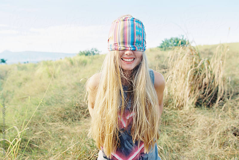blonde girl with rainbow stripe headband pulled down over her eyes by wendy laurel for Stocksy United