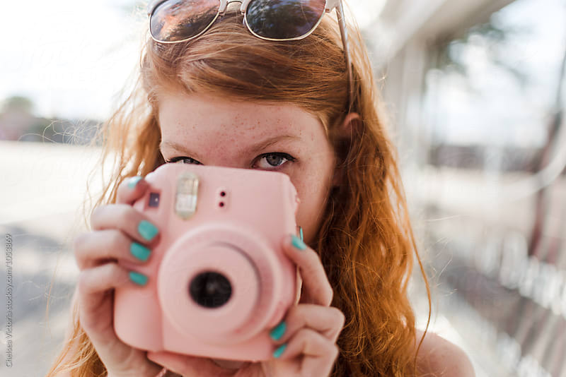 A teenage girl taking a photograph with a film camera by Chelsea Victoria for Stocksy United