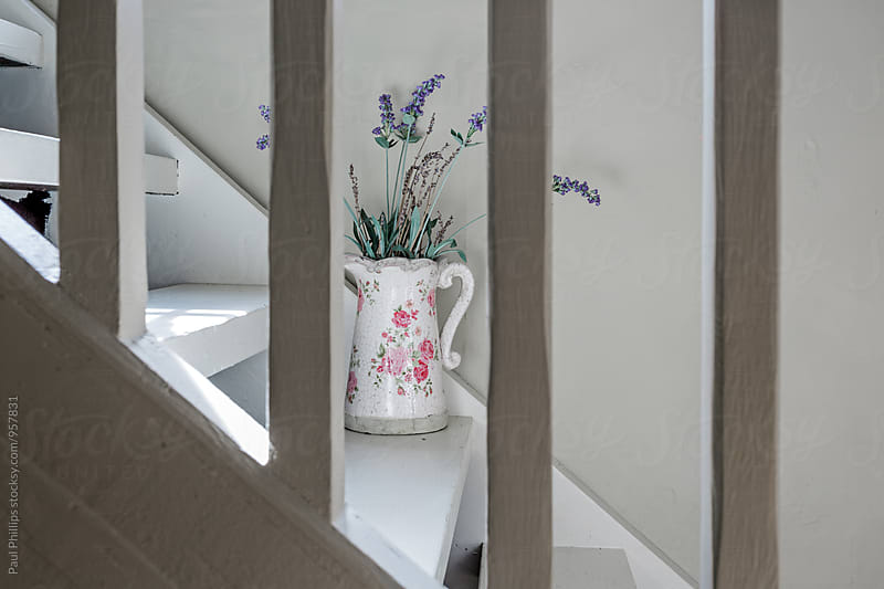 Flowers in an old jug standing on stairs. by Paul Phillips for Stocksy United