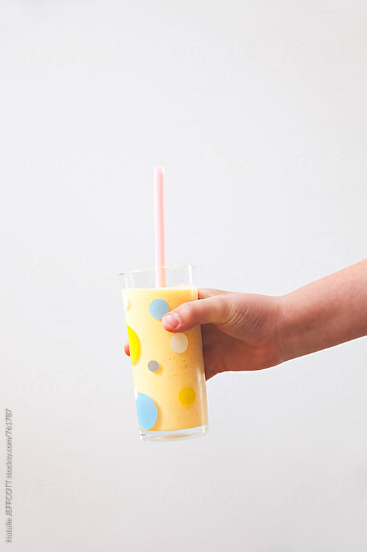 A child's hand holding a homemade mango lassi against a white wall by Natalie JEFFCOTT for Stocksy United
