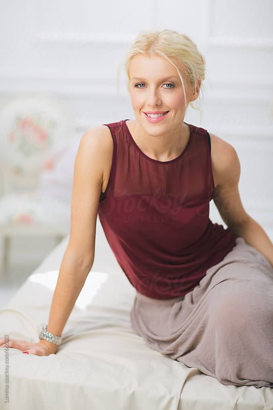 Beautiful Smiling Woman Sitting on Bed by Lumina for Stocksy United