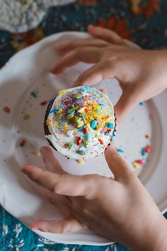 Children's hands reaching for cupcake by Carey Shaw for Stocksy United