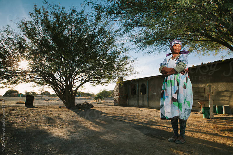 Proud Nama woman standing outside her home by Micky Wiswedel for Stocksy United